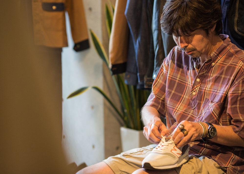 ニューバランススニーカーの靴紐を結ぶ鈴木さん